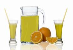 Jarra y dos vidrios de jugo, anaranjados en el fondo blanco Fotos de archivo