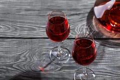 Jarra y dos vidrios de vino rojo en una tabla de madera Foto de archivo libre de regalías