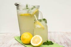 Jarra y taza de cristal de limonada en el fondo blanco Imagen de archivo