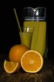 Jarra y un vidrio de jugo, anaranjado Imagenes de archivo