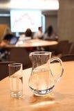 Jarra y vidrio con agua clara limpia en el vector Foto de archivo libre de regalías