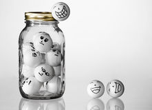 Jarred Up. Conceptual Image - Trapped, Escaping, Overworked, etc. Ping Pong balls in a jar with bored faces on them, and happy ones escaping from the jar Royalty Free Stock Photos