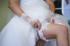 Jarretière de port sur la jambe de la jeune mariée Photographie stock libre de droits