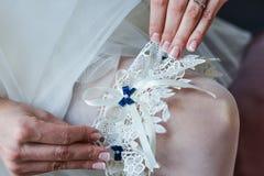 Jarretière sur la jambe d'une jeune mariée, moments de jour du mariage Photographie stock libre de droits