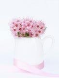Jarro branco com o ramalhete de flores cor-de-rosa em um fundo branco Foto de Stock