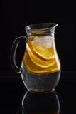 Jarro com água, as laranjas cortadas e o gelo no fundo preto imagens de stock royalty free