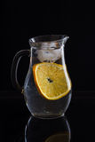 Jarro com água, gelo e laranja no fundo preto foto de stock royalty free