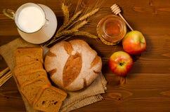 Jarro con leche, las espiguillas, el pan de centeno, la miel y las manzanas en una tabla de madera, visión superior Imagen de archivo libre de regalías