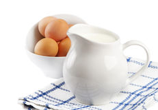 Jarro con leche y huevos imagenes de archivo