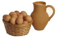 Jarro da argila com leite e uma cesta dos ovos Fotos de Stock