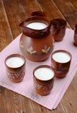 Jarro da argila e três copos do leite em uma tabela de madeira Imagem de Stock Royalty Free