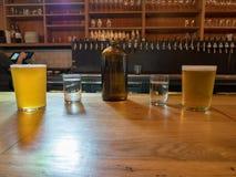 Jarro de água, copos, e cerveja no contador da barra na cervejaria Fotos de Stock Royalty Free