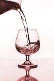 Jarro de agua que vierte a la copa de vino Foto de archivo libre de regalías