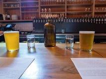 Jarro de agua, tazas, cerveza, menús del brunch en contador de la barra Foto de archivo libre de regalías