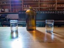Jarro de agua y tazas encima de la barra de la cervecería Fotos de archivo