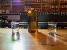 Jarro de agua y tazas encima de la barra de la cervecería Imagen de archivo libre de regalías