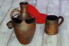 Jarro de cerámica con las gafas de sol, taza de cerámica y gorra de béisbol brillante roja en fondo de madera ligero Concepto sim fotografía de archivo libre de regalías