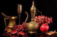 Jarro de cobre, granada roja y uvas rosadas en un backgroun negro Imagen de archivo