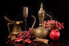 Jarro de cobre, granada roja y uvas rosadas en un backgroun negro Fotografía de archivo