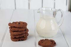Jarro de cristal con las galletas de microprocesador de la leche y de chocolate foto de archivo
