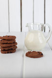 Jarro de cristal con las galletas de microprocesador de la leche y de chocolate imagenes de archivo