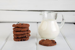 Jarro de cristal con las galletas de microprocesador de la leche y de chocolate fotos de archivo