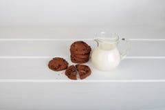 Jarro de cristal con las galletas de microprocesador de la leche y de chocolate imagen de archivo