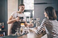 Jarro de cristal y sonrisa del café de la tenencia amistosa del barista imagenes de archivo