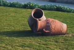 Jarro de la ánfora de dos arcillas, floreros de cerámica viejos en césped de la hierba verde cerca del mar Imagen de archivo libre de regalías