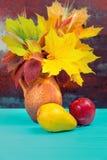 Jarro de la arcilla con las hojas y el trigo de otoño cerca de una manzana y de una pera o Imagen de archivo libre de regalías