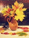Jarro de la arcilla con las hojas y el trigo de otoño en el escritorio de madera blanco Foto de archivo libre de regalías