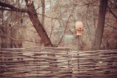 Jarro de la arcilla en una cerca de mimbre Foto de archivo libre de regalías