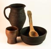Jarro de la arcilla, taza, cuenco y cuchara de madera Imágenes de archivo libres de regalías