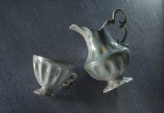 Jarro de la taza y de leche en la tabla Imagen de archivo libre de regalías