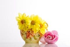 Jarro de leche antiguo de China con las flores amarillas y rosadas contra pizca Fotografía de archivo libre de regalías