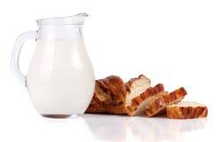 Jarro de leche con una barra de pan aislada en el fondo blanco Imagenes de archivo