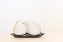 Jarro de leche y tazón de fuente de azúcar Foto de archivo libre de regalías