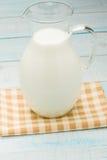 Jarro de leite em uma toalha de mesa quadriculado amarela Imagem de Stock Royalty Free
