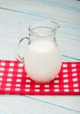 Jarro de leite em uma toalha de mesa quadriculado vermelha Imagens de Stock