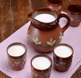 Jarro de leite na tabela de madeira Fotos de Stock