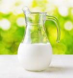 Jarro de leite no fundo da natureza. Jarro meio cheio Imagens de Stock