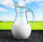 Jarro de leite no fundo do prado. Jarro meio cheio Foto de Stock Royalty Free