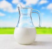 Jarro de leite no fundo do prado. Jarro meio cheio Fotografia de Stock