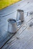 Jarro de leite pequeno na tabela de madeira velha Imagem de Stock