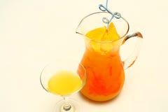 Jarro de zumo de naranja con el vidrio Imagen de archivo