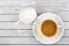 Jarro del café sólo y de la crema en una tabla de madera Fotografía de archivo libre de regalías