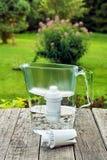 Jarro do filtro de água com um cartucho substituível na tabela de madeira áspera no jardim do verão imagem de stock
