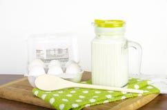 Jarro do leite com uma caixa de ovos com batedor de ovos Fotos de Stock