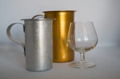 Jarro dourado e prateado com o vidro do conhaque vazio no fundo branco foto de stock