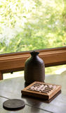 Jarro na tabela com pousas-copos Foto de Stock Royalty Free